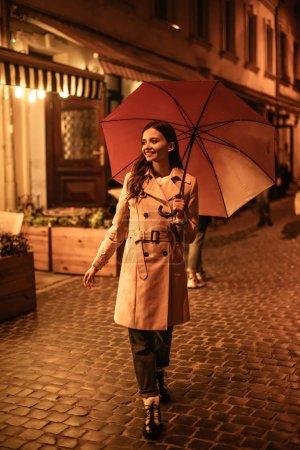 Photo pour Jeune femme joyeuse marchant dans la rue le soir avec un parapluie - image libre de droit