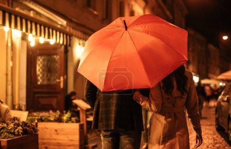 Photo pour Vue arrière du couple en tenue d'automne marchant sous le parapluie le long de la rue du soir - image libre de droit