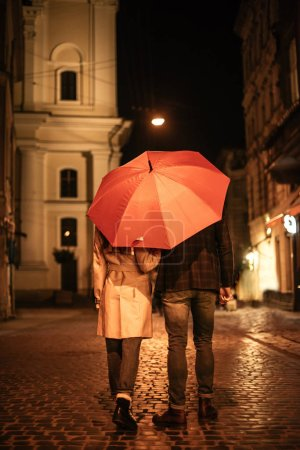 Photo for Back view of couple in autumn outfit walking under umbrella along evening street - Royalty Free Image