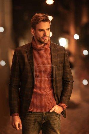 Photo pour Bel homme confiant en tenue d'automne regardant loin et tenant la main dans la poche tout en se tenant debout sur la rue du soir - image libre de droit