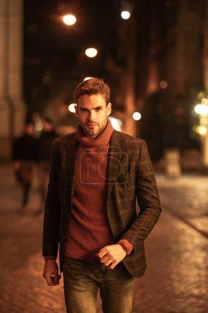 Photo pour Bel homme confiant en tenue d'automne regardant la caméra tout en marchant sur la rue du soir - image libre de droit