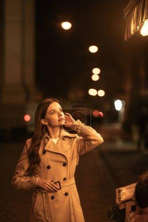 Photo pour Chère jeune femme en trench coat regardant loin et touchant les cheveux tout en se tenant debout sur la rue du soir - image libre de droit