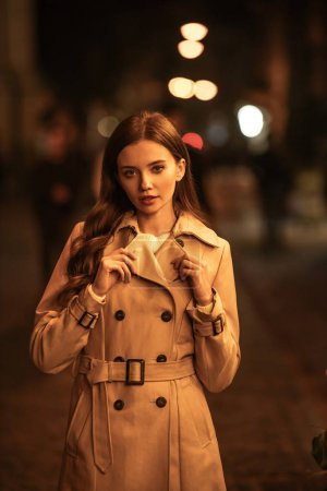 Photo pour Attractive, confident woman in trench coat looking at camera while standing on evening street - image libre de droit