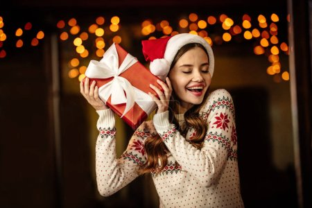 Photo for Amazed young woman in warm sweater and santa hat holding gift box with closed eyes - Royalty Free Image
