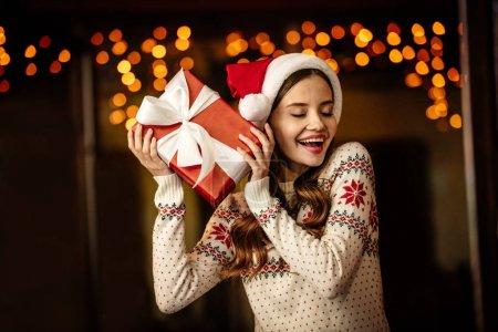 Photo pour Étonnante jeune femme en pull chaud et chapeau santa tenant boîte cadeau avec les yeux fermés - image libre de droit