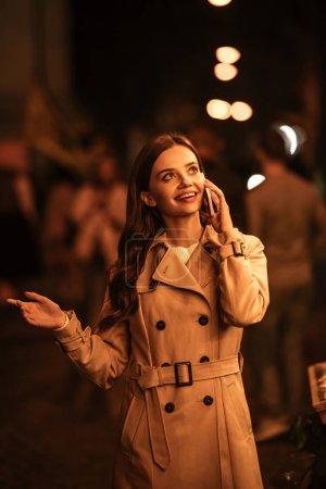 Photo pour Jolie, fille souriante regardant loin tout en parlant sur smartphone sur la rue du soir - image libre de droit