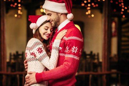 Photo pour Heureux jeune couple dans santa chapeaux et chandails chauds embrassant les yeux fermés - image libre de droit