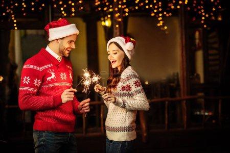 Foto de Jovencita pareja alegre en sombreros de santa y sudor caliente sosteniendo a los ahorradores en la víspera de las navidades. - Imagen libre de derechos
