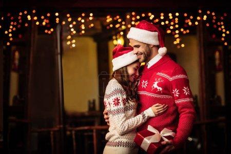 Photo pour Heureux couple en chandails chauds et chapeaux de Père Noël embrassant sur la rue - image libre de droit