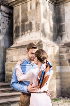 Photo for Happy, stylish couple of tourists embracing while walking on street - Royalty Free Image