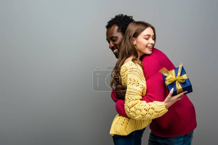 Photo for Happy interracial couple in sweaters holding present and hugging on grey background - Royalty Free Image