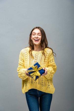 Photo pour Petite fille heureuse en chandail jaune tenant présent isolée sur gris - image libre de droit