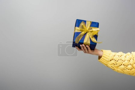 Photo for Cropped view of girl in yellow sweater holding present isolated on grey - Royalty Free Image