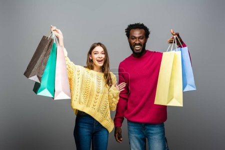 Photo for Happy interracial couple in sweaters holding hands and shopping bags on grey background - Royalty Free Image