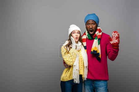 Photo for Surprised interracial couple in winter outfit hugging on grey background - Royalty Free Image