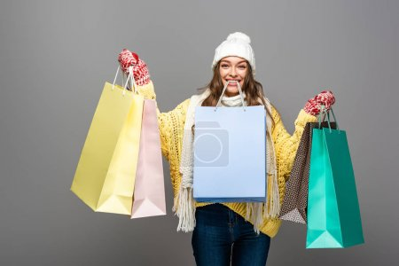 Photo for Happy woman in winter outfit with shopping bags on grey background - Royalty Free Image