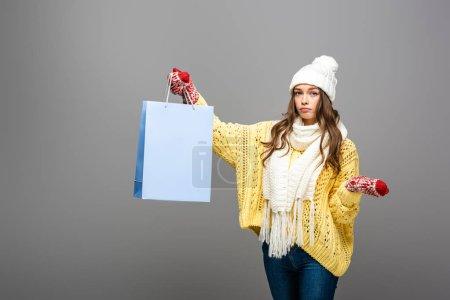 Photo pour Femme triste en tenue d'hiver avec sac à provisions sur fond gris - image libre de droit