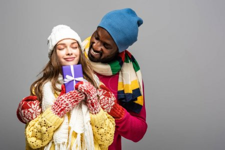 Photo for Happy interracial couple in winter outfit holding present isolated on grey - Royalty Free Image