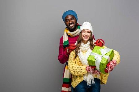 Photo pour Heureux couple interracial en tenue d'hiver exploitation présente isolé sur gris - image libre de droit