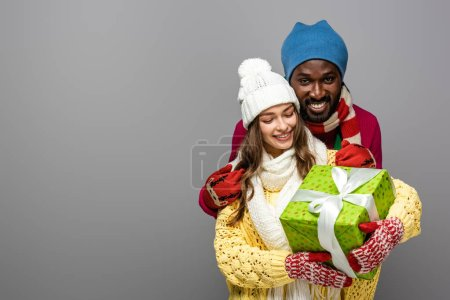 smiling interracial couple in winter outfit holding present isolated on grey