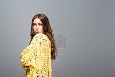 Photo pour Vue latérale de la femme offensée en pull jaune avec les bras croisés sur fond gris - image libre de droit
