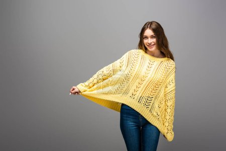 Photo for Happy woman holding yellow sweater on grey background - Royalty Free Image