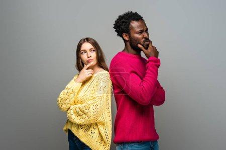 Photo pour Un couple interracial réfléchi en chandails tricotés se tenant dos à dos sur fond gris - image libre de droit