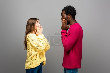 Photo for Shocked interracial couple in knitted sweaters looking at each other on grey background - Royalty Free Image