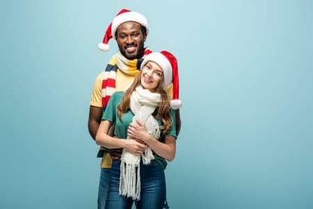 Photo for Happy interracial couple in santa hats and scarves hugging isolated on blue - Royalty Free Image