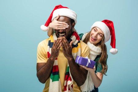 Photo pour Heureuse fille dans santa chapeau et écharpe couvrant les yeux sur afro-américain copain et cadeau isolé sur bleu - image libre de droit