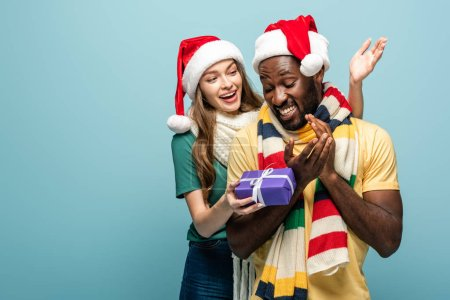 Photo for Happy girl in santa hat and scarf gifting present to african american boyfriend isolated on blue - Royalty Free Image