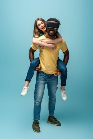 happy girl piggybacking on african american boyfriend in vr headset on blue background