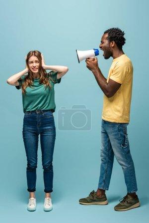 Photo pour Un Américain d'origine africaine en colère crie en mégaphone devant une copine qui se couvre les oreilles avec les mains sur fond bleu - image libre de droit