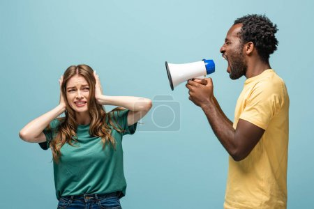 angry african american man screaming in megaphone at girlfriend covering ears with hands on blue background