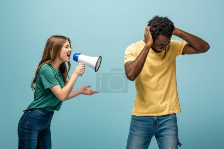 Photo for Angry girl screaming in megaphone at african american boyfriend covering ears with hands on blue background - Royalty Free Image