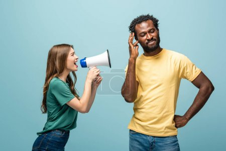 Photo for Angry girl screaming in megaphone at african american boyfriend on blue background - Royalty Free Image