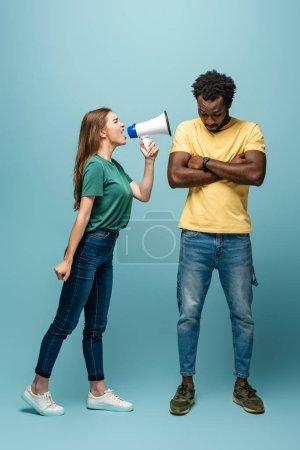 Photo pour Fille en colère criant en mégaphone au petit ami afro-américain avec les bras croisés sur fond bleu - image libre de droit