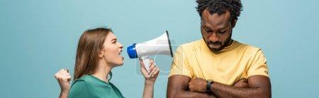 Photo pour Fille en colère criant en mégaphone devant un copain américain africain aux bras croisés sur fond bleu - image libre de droit