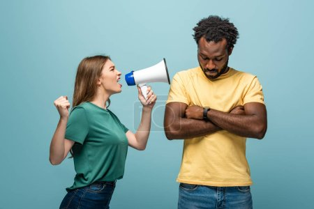 angry girl screaming in megaphone at african american boyfriend with crossed arms on blue background