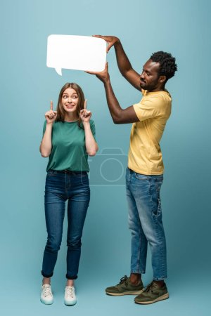 african american man holding speech bubble above girlfriend showing idea gesture on blue background