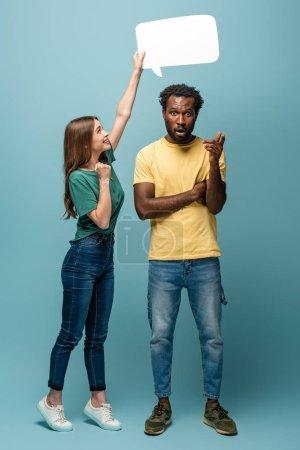 fille tenant bulle de discours au-dessus de l'homme afro-américain montrant geste idée sur fond bleu