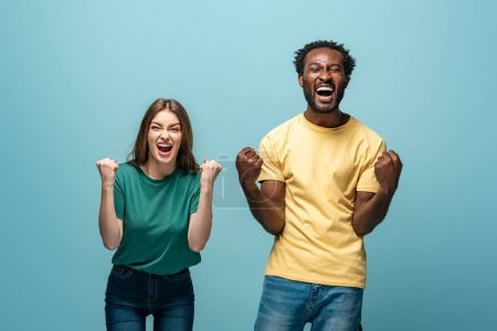 Photo for Happy interracial couple showing yes gesture on blue background - Royalty Free Image