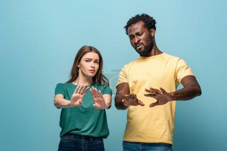 Photo pour Couple interracial confus ne montrant aucun geste sur fond bleu - image libre de droit