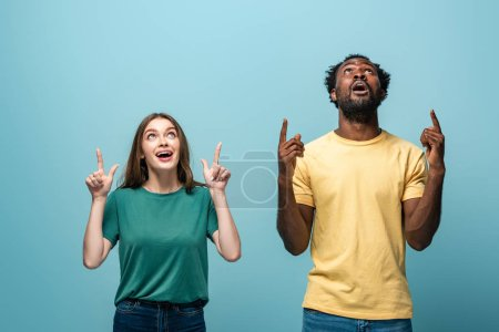 shocked interracial couple pointing with fingers up on blue background