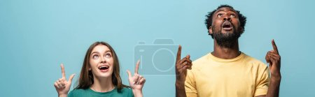 Photo for Shocked interracial couple pointing with fingers up on blue background, panoramic shot - Royalty Free Image