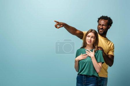 Photo pour Confus couple interracial pointant du doigt sur fond bleu - image libre de droit