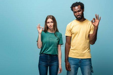 Photo pour Mécontent couple interracial montrant ok signe sur fond bleu - image libre de droit