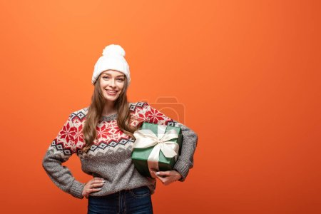 happy girl in winter outfit holding present on orange background