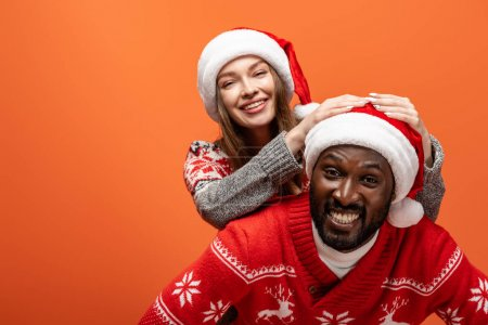 happy interracial couple in santa hats and Christmas sweaters on orange background