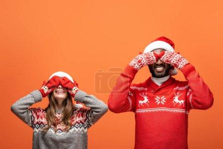 Photo pour Heureux couple interracial dans santa chapeaux, mitaines et pulls de Noël couvrant les yeux avec les mains sur fond orange - image libre de droit